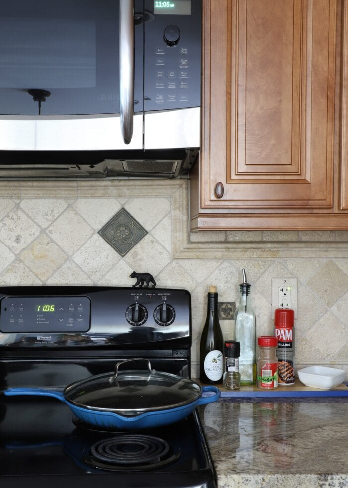 Vertical picture of a kitchen range with black stove, microwave, and a blue skillet.