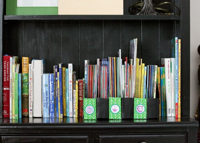 Kids books organized on a black shelf in DIY Book Organizers made from cereal boxes.