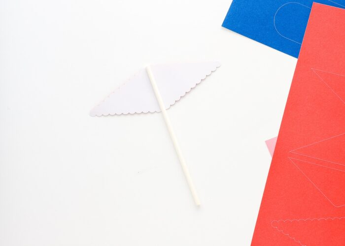 White stick laid onto a cupcake topper pennant