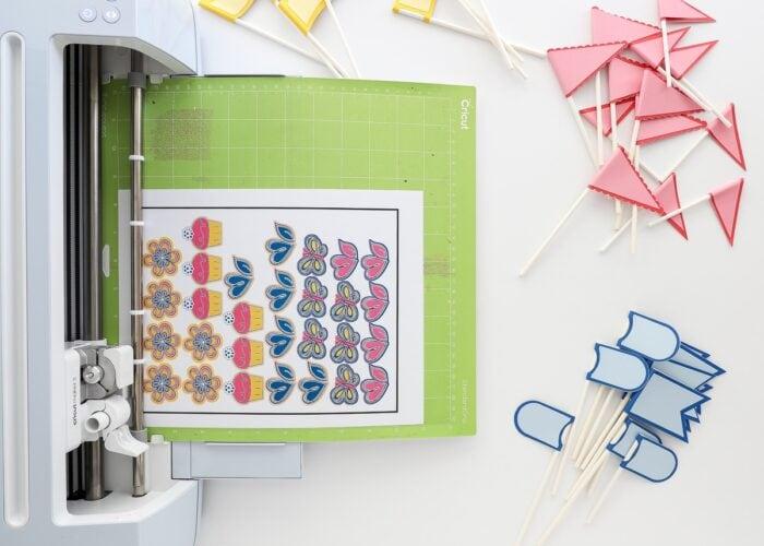 Cricut Maker 3 cutting printed birthday stickers.