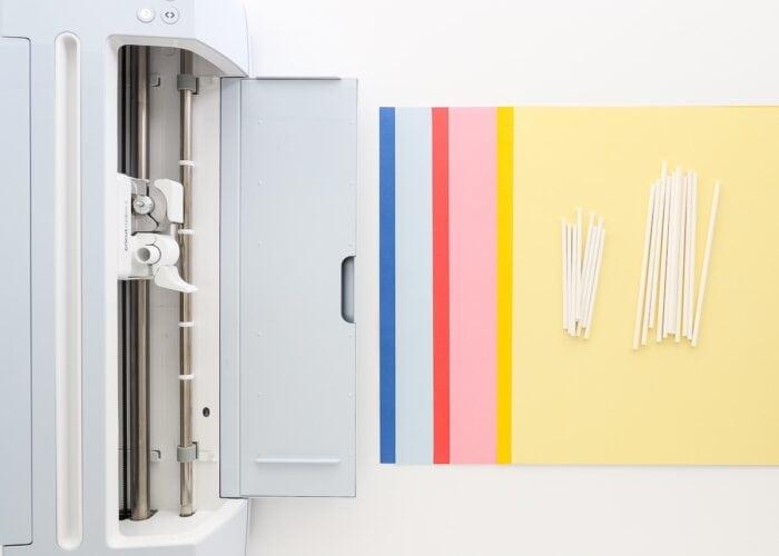 Cricut Maker 3 shown with Smart Paper Sticker Cardstock and lollipop sticks