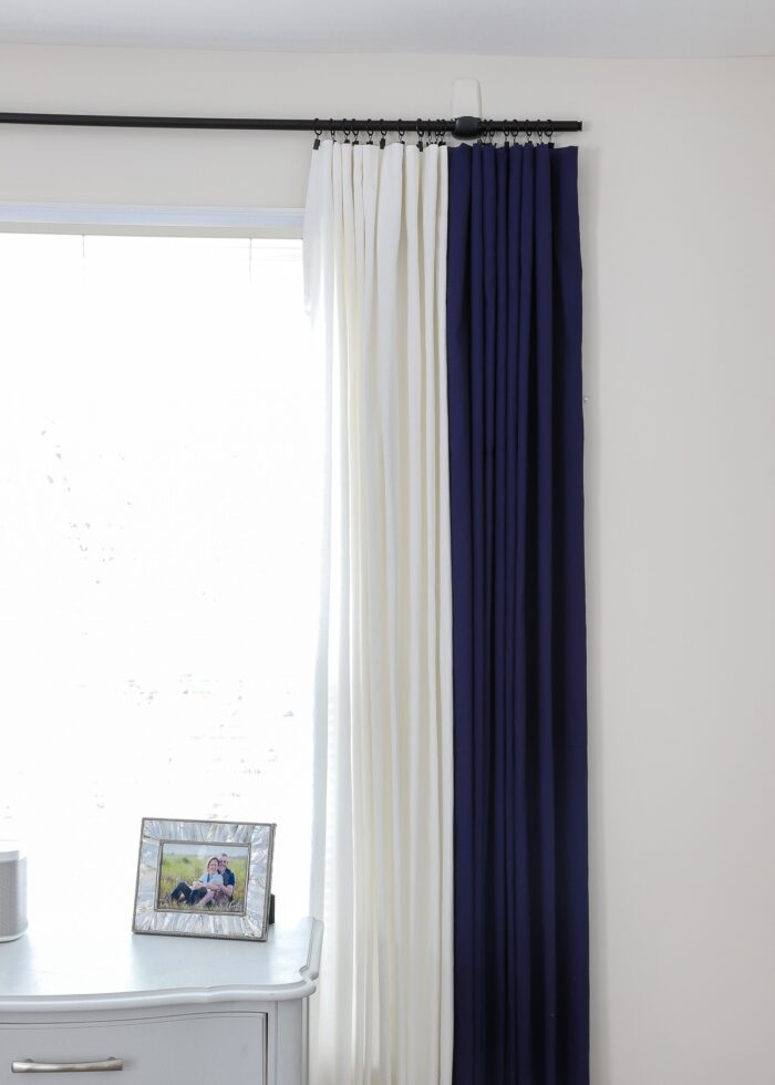 Navy and white curtains hung on a black curtain rod with black curtain rings