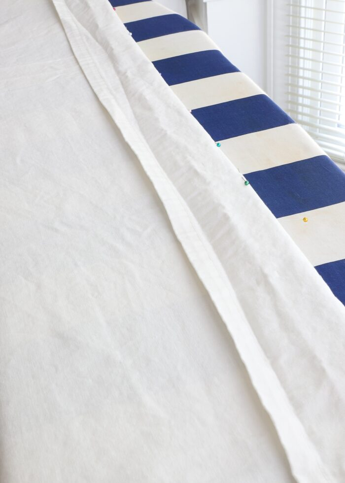 White curtain with hem folded over on an ironing board