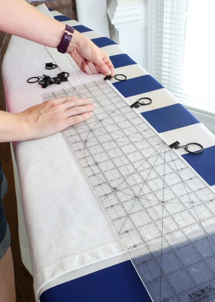 Black curtain ring clips being added to the top of a white curtain panel