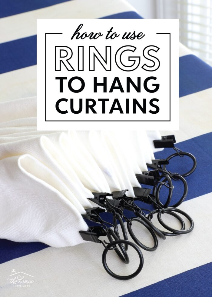 Black curtain rings on the top of a white curtain panel