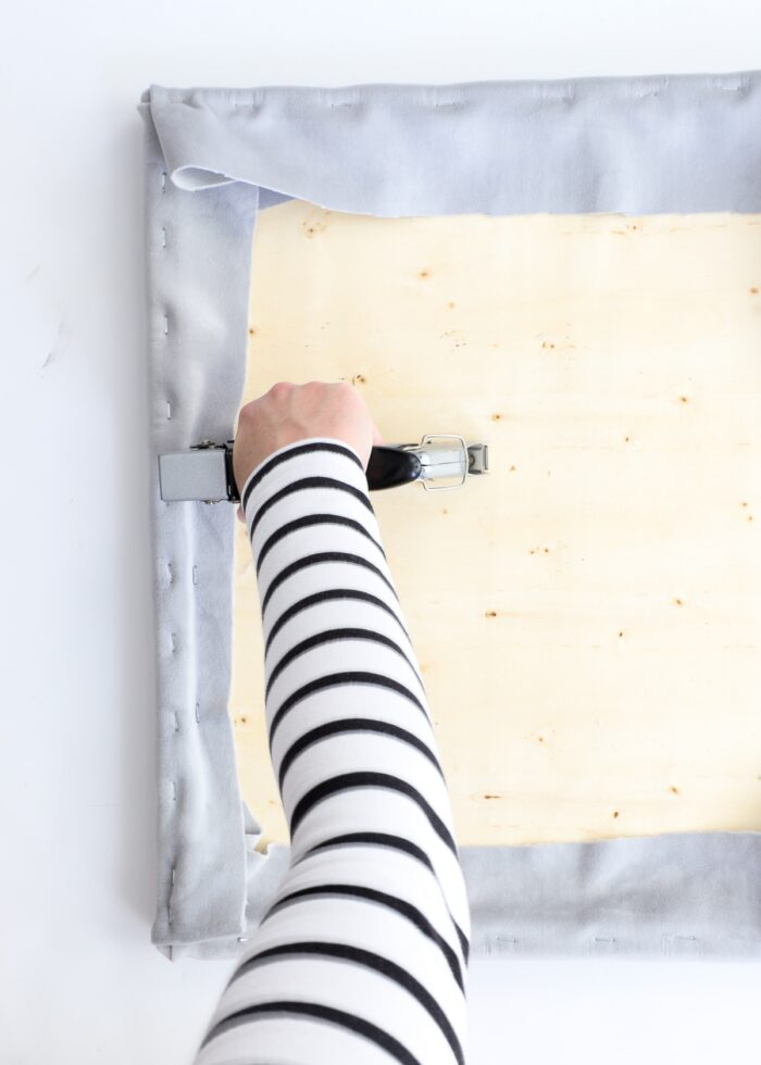 Hands using a staple gun to recover a bench cushion in grey fabric.