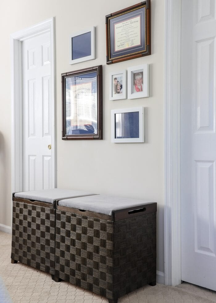 Two wooden hampers with light grey recovered cushion cover seats against a gallery wall.
