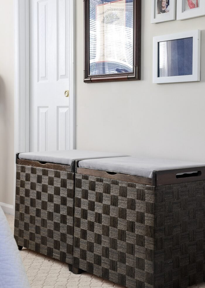 Two wooden hampers with cushions recovered in grey velvet fabric against a tan wall with frames.