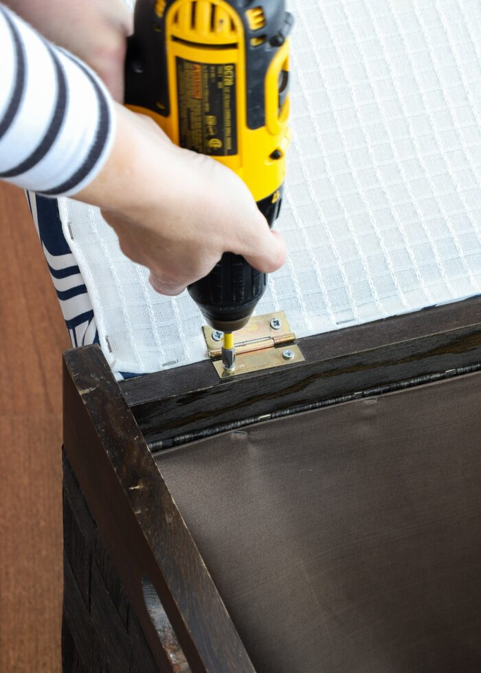 Hands holding drill to remove lid on wooden hamper.