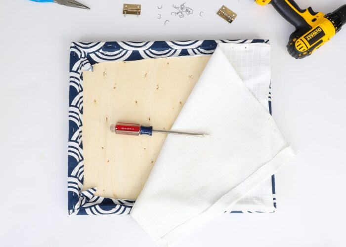 Cushion with fabric being removed with tools.