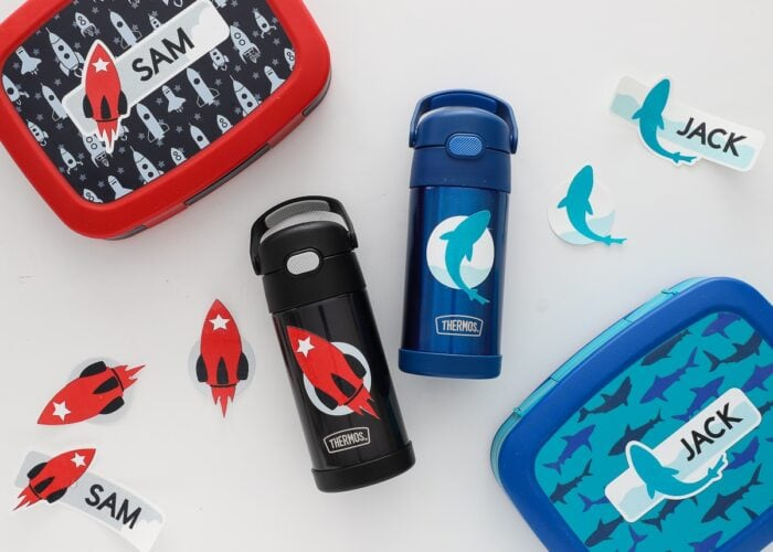 Coordinating lunch boxes and water bottles with personalized labels.