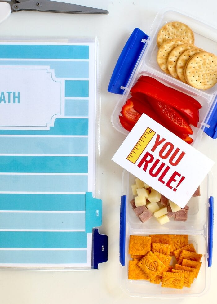 School binder shown alongside Sistema lunch boxes loaded with snacks and a lunch box note.