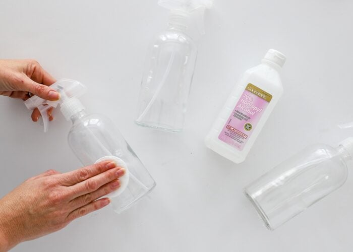 Glass spray bottles shown with hands cleaning with rubbing alcohol.