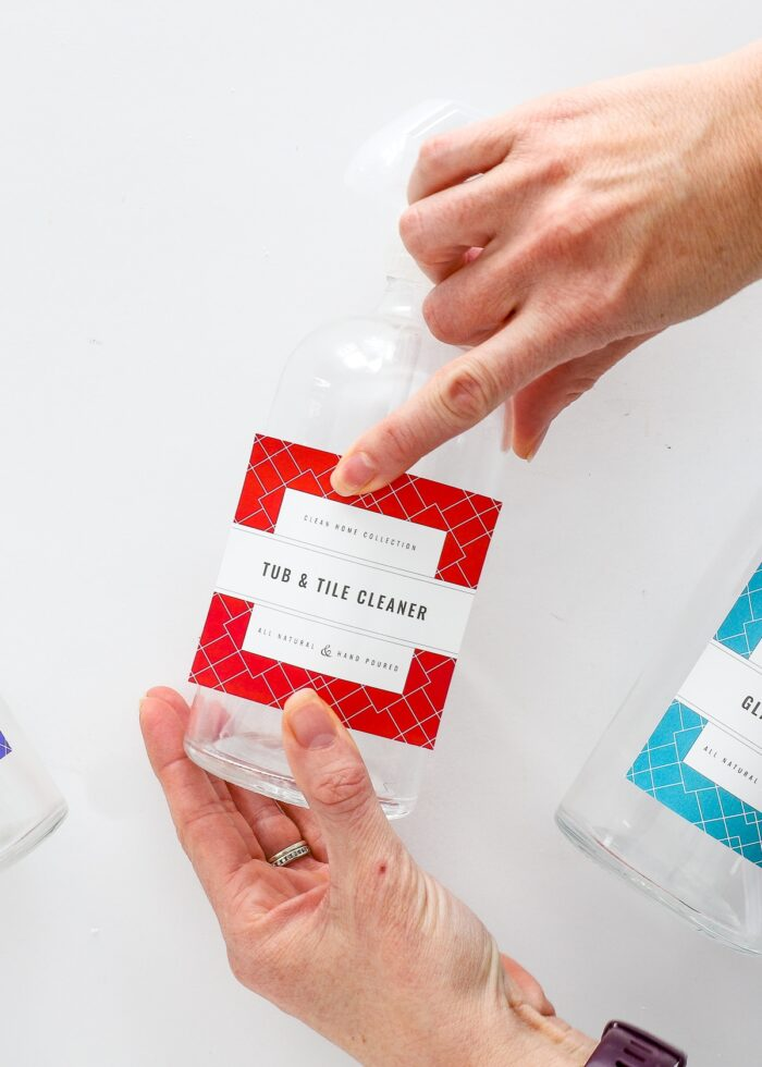 Hands applying a red waterproof printable cleaning label onto a glass spray bottle.
