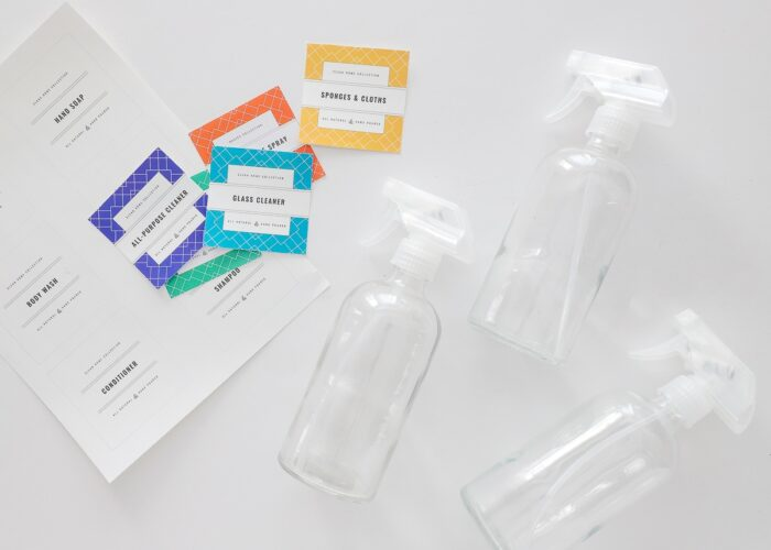 Glass spray bottles shown with colorful printable cleaning supply labels.