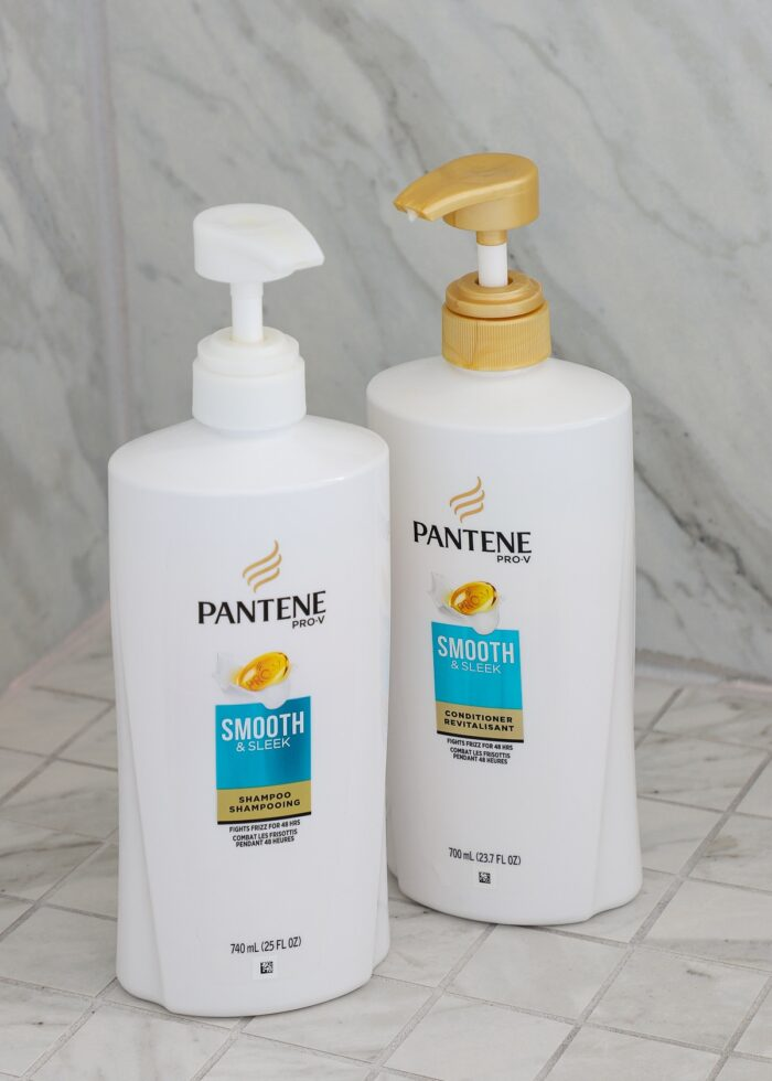 White shampoo and conditioner bottles in a marble shower.