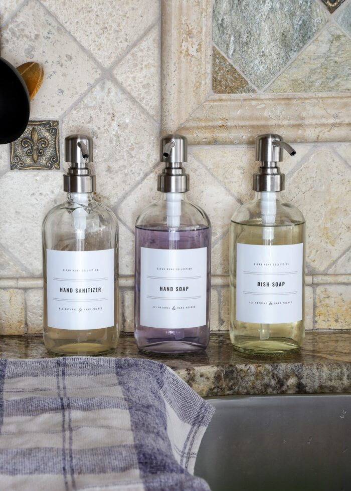 Glass soap dispensers with black-and-white printable labels against a stone kitchen backsplash..