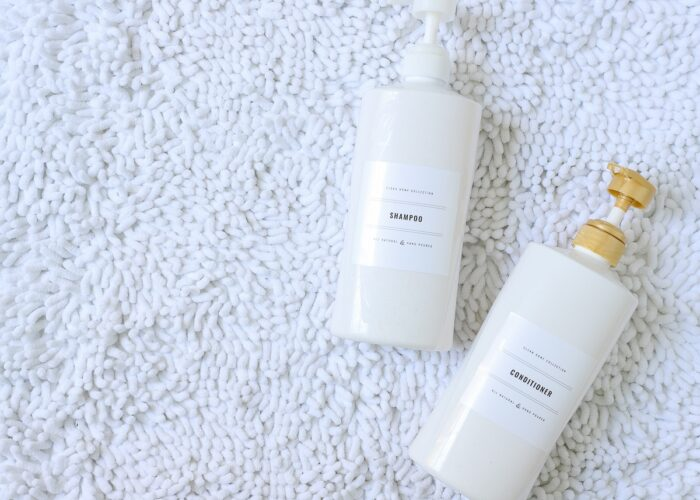 White shampoo and conditioner bottles on a white carpet with black-and-white printable labels.