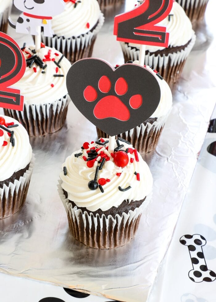 Chocolate cupcakes with white frosting and adorable dog paw cake toppers made from paper.