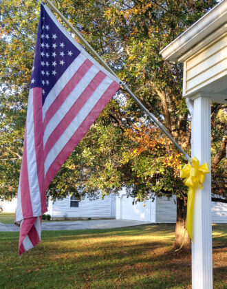 American flag on white house with yellow ribbon.