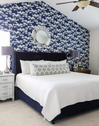 Rental bedroom with blue and white flowered wallpaper, a navy bed, and grey lamps.